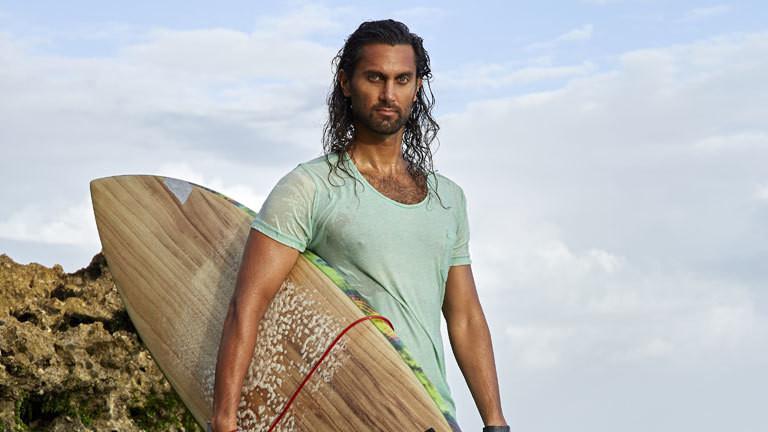 Afridun Amu mit einem Surfbrett unter dem Arm.