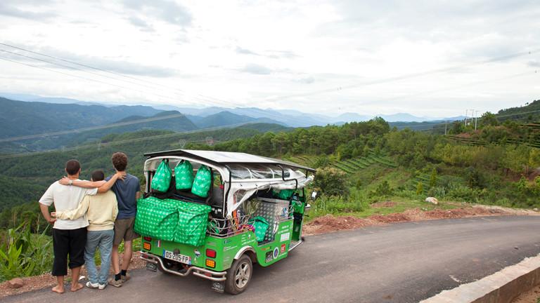 Drei Männer umarmen sich neben einem grünen Tuk-Tuk vor Bergkulisse.