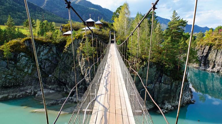Eine Brücke über einem Abhang vor blauem Wasser.