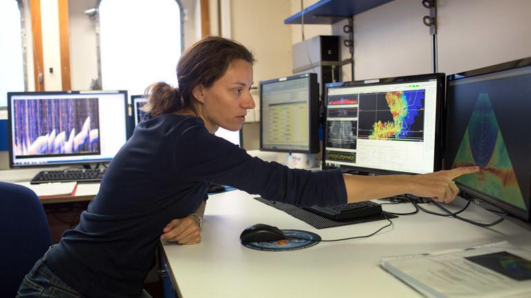 Miriam Römer zeigt auf einen Bildschirm