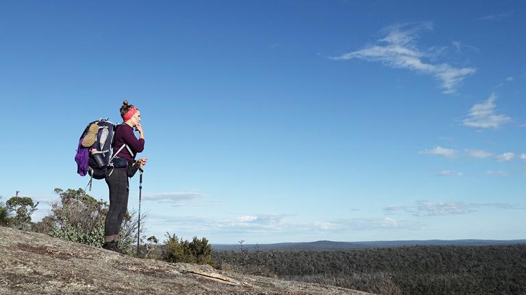 Kathrin Heckmann mit Wanderausrüstung blickt in ein Tal.