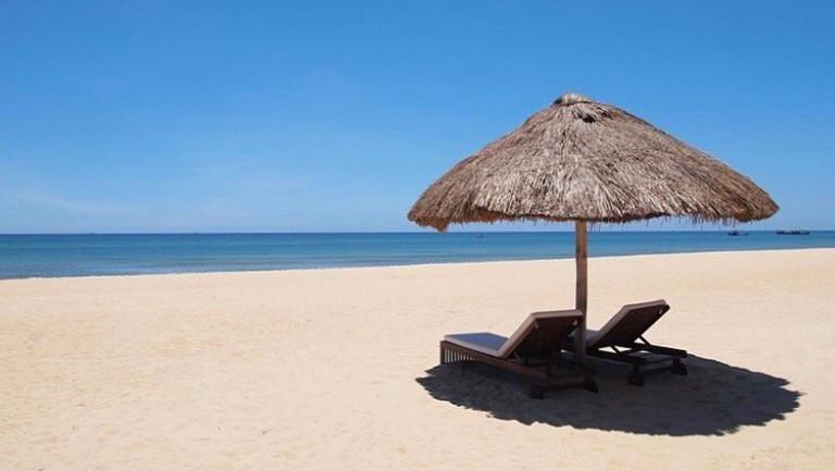 An einem leeren Strand von Zentralvietnam stehen zwei leere Liegen mit Sonnenschirm.
