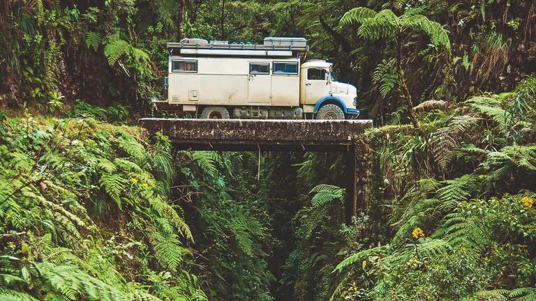 Ein Oldtimer-LKW auf einer winzigen Brücke über einer Schlucht in Bolivien.