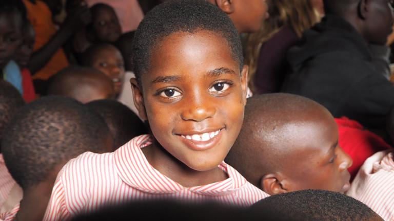 Ein Mädchen im Masaka District, Uganda. Ihre Grundschule hat einen Wassertank, der Regenwasser auffängt, damit die Kinder mit Trinkwasser versorgt werden.