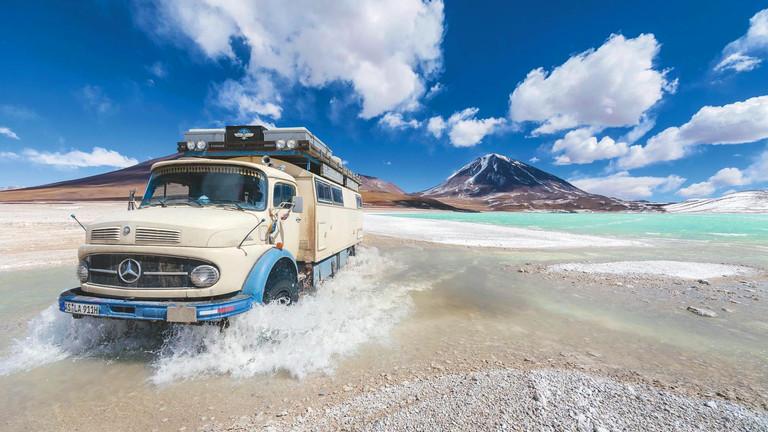 Ein Oldtimer fährt durch eine grüne Lagune in Bolivien.