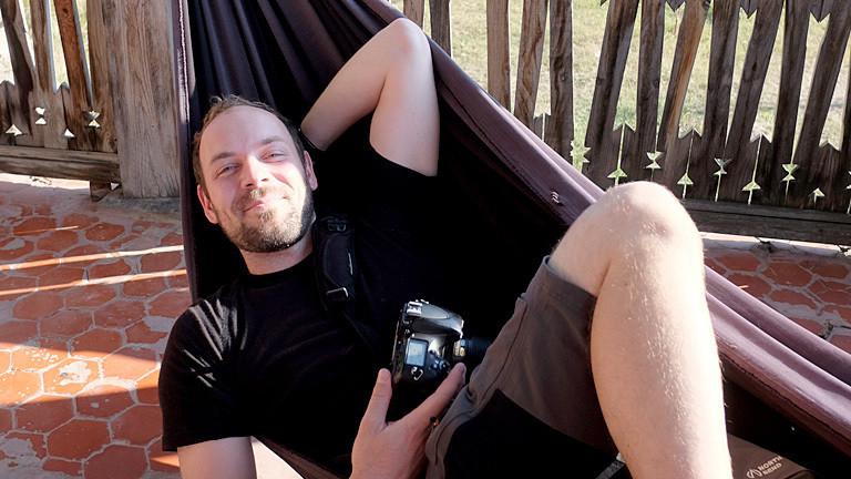 Mann mit Kamera in einer Hängematte