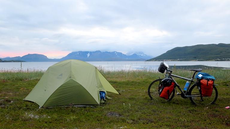 Rad und Zelt vor einem Fluss