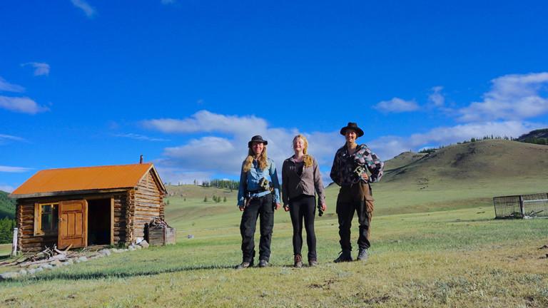 Drei Frauen vor einer Hütte
