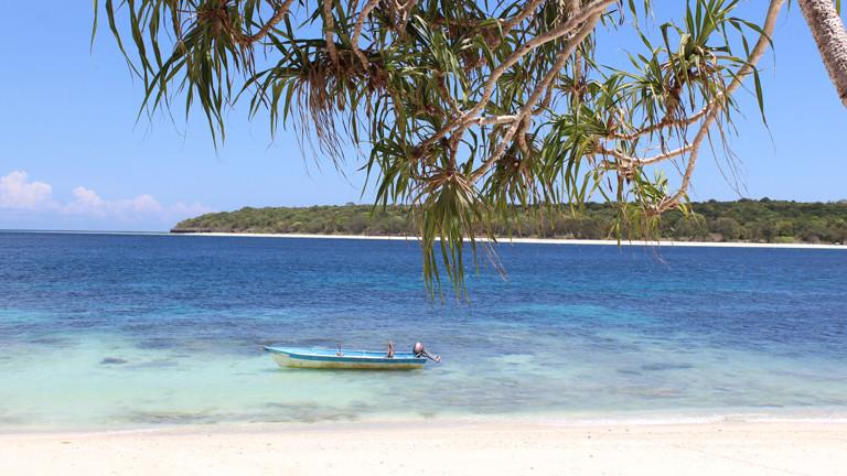 Strand, Sand und ein kleiner Boot im Meer.