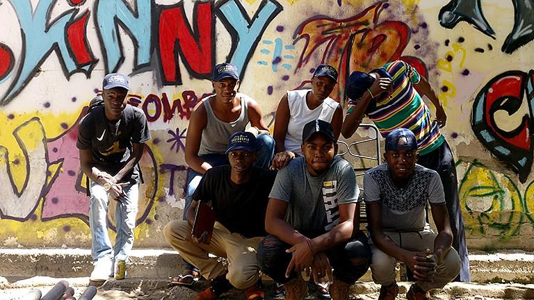 Schwarze Männer und Frauen vor einer Graffiti-Wand.
