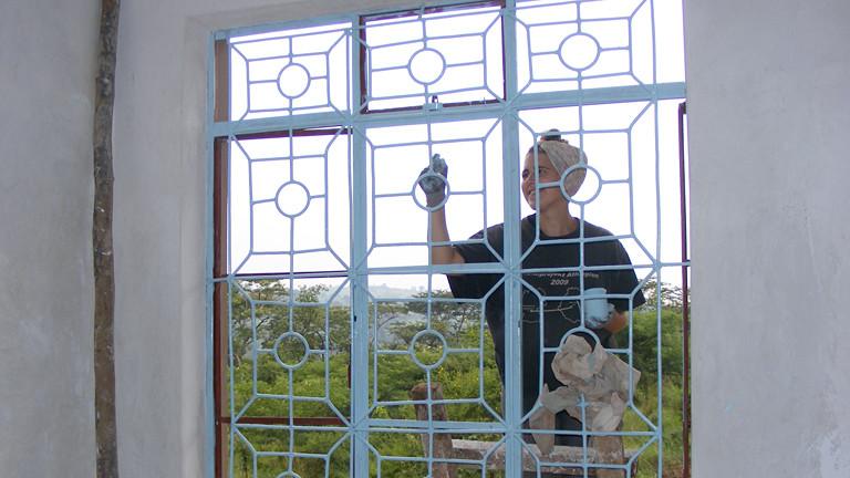 Eine Frau beim Fenster streichen.