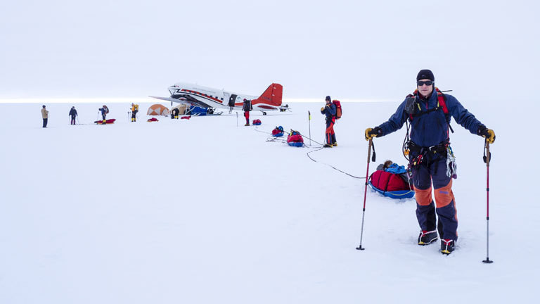 Mit Skiern auf dem vereisten Gipfel eines Vulkans.