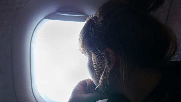 Eine Frau schaut aus dem Fenster eines Flugzeugs.