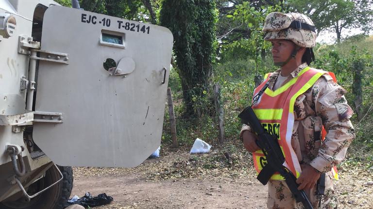 Ein Soldat des kolumbianischen Militärs steht schwer bewaffnet an einem Kontrollposten an einem Farc-Entwaffnungscamp.