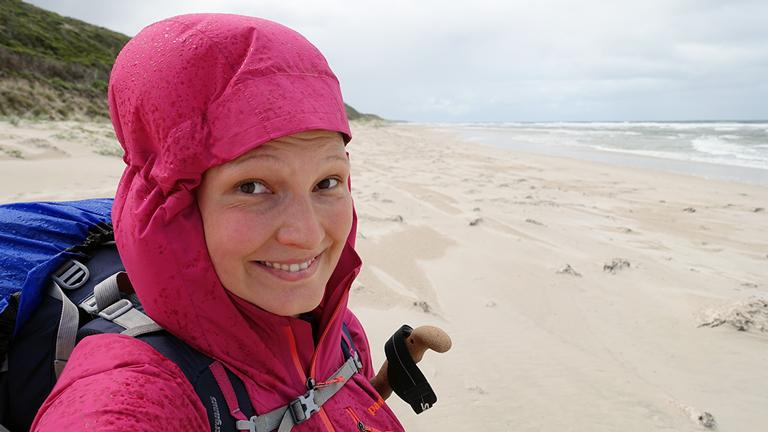 Kathrin Heckmann, mit Kapute vor dem Regen geschützt, lächelt in die Kamera, im Hintergrund die australische Küste.