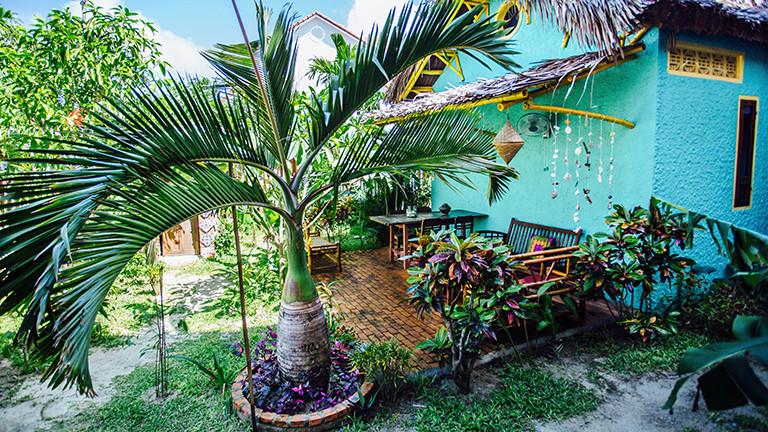 Blick auf das Hostel Happy Bird mit Garten. Es sieht sehr gemütlich aus.