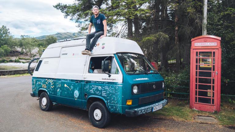 Marten Berger sitzt auf dem Dach seines VW-Busses