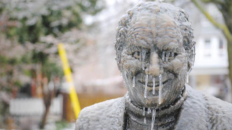 Eiszapfen im Gesicht einer Statue von einem Mann.