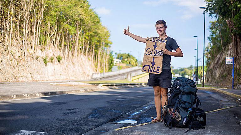 Joshi Nichell als Tramper am Straßenrand mit Pappschild