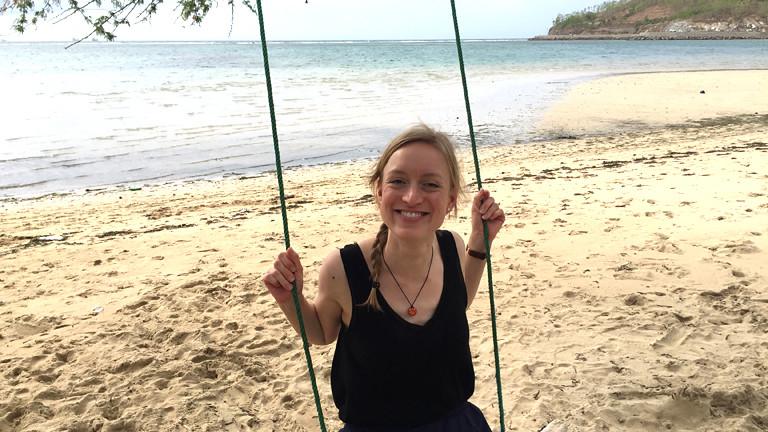 Frau auf einer Schaukel am Strand