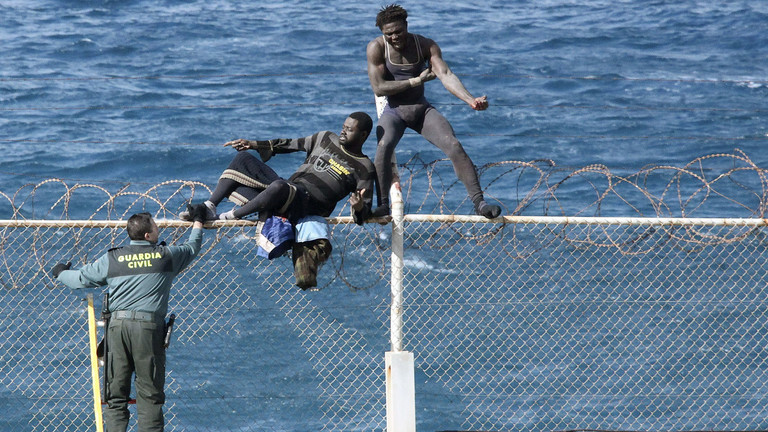 Two immigrants try to jump over the Ceuta border fence