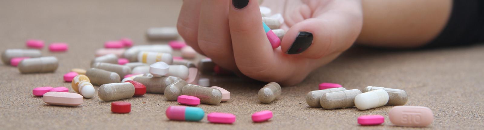 Hand mit schwarz lackierten Fingernägeln und vielen bunten Pillen.