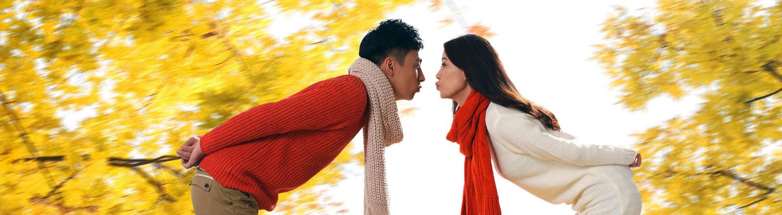 Ein chinesisches Päärchen steht sich gegenüber, kurz davor, sich zu küssen