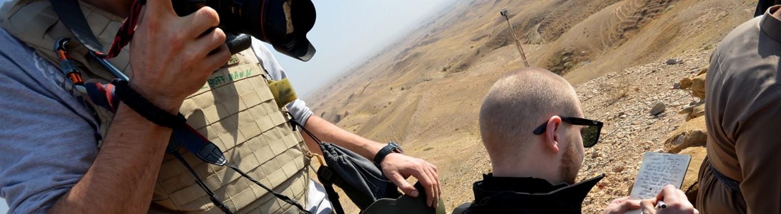 Fotograf mit Kamera und Journalist in der Wüste