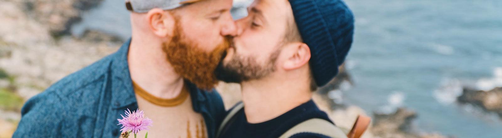 Zwei Männer küssen sich.