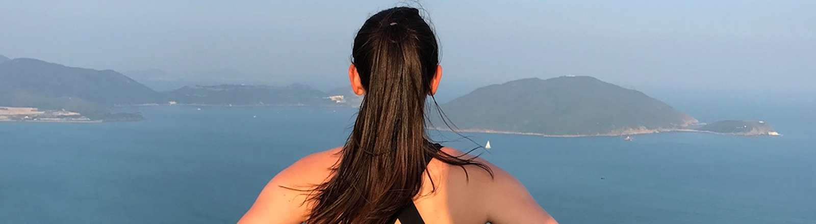 Frau vor einer Landschaft am Meer