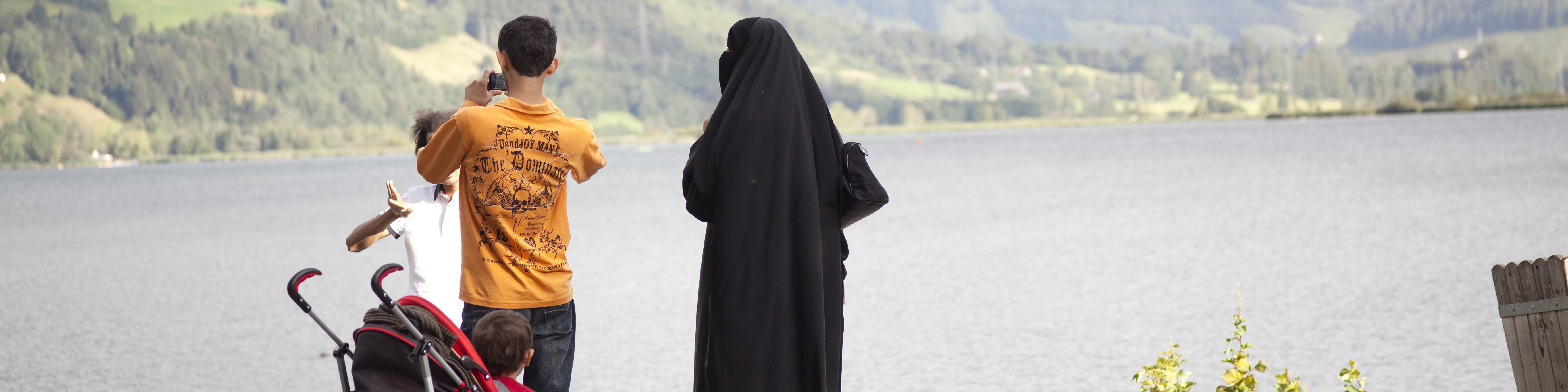 Eine verhüllte Frau mit ihrem Kind und ihrem Mann am See