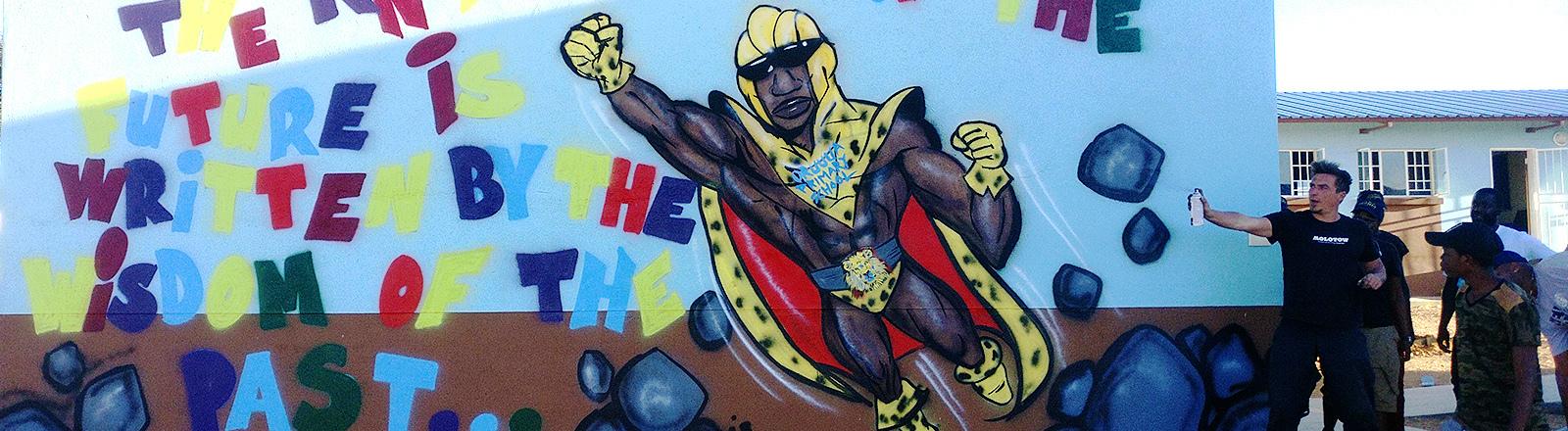 Mann hält eine Sprühdose an ein Superheld-Graffiti.