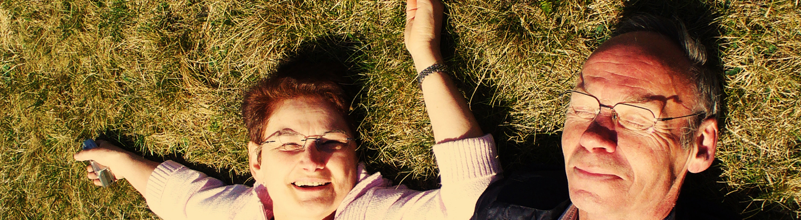 Ein älteres Paar liegt im Gras
