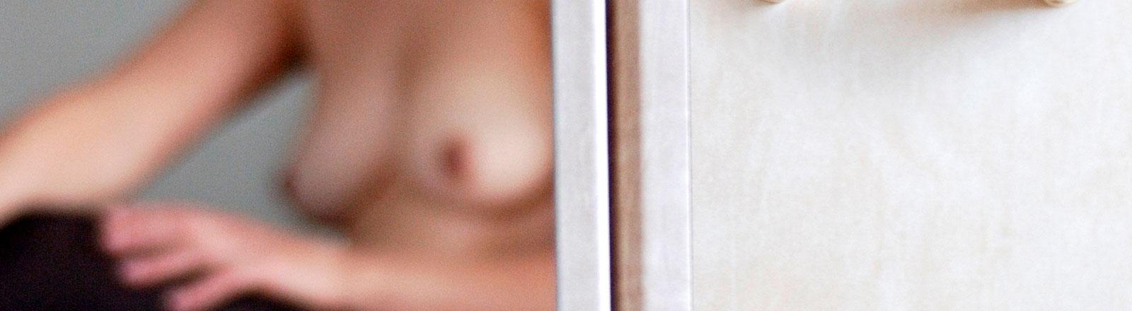 Eine Frau mit nackten Brüsten sitzt hinter einer Tür und wartet.