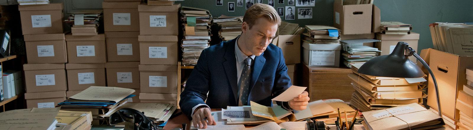 """Der junge Staatssanwalt Johann Radmann (Alexander Fehling) bei seiner Recherche nach Nazi-Verbrechern - eine Szene des Films """"Im Labyrinth des Schweigens"""""""