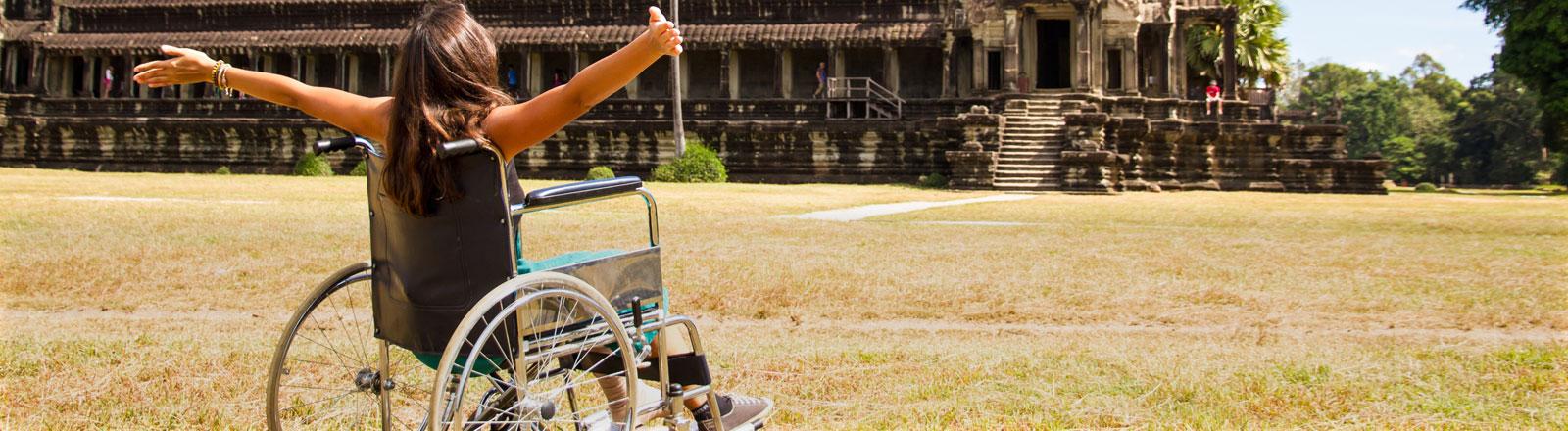 Eine Frau sitzt in einem Rollstuhl und breitet die Arme aus.