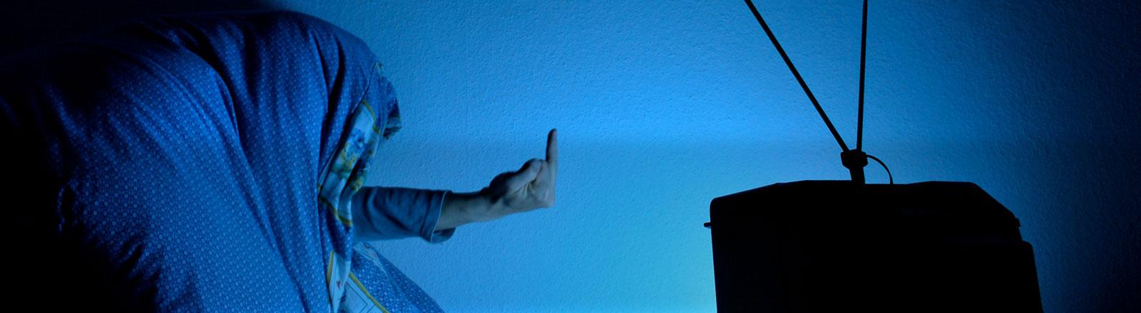 Ein Mann unter einer Bettdecke zeigt einem Fernsehen den Stinkefinger.