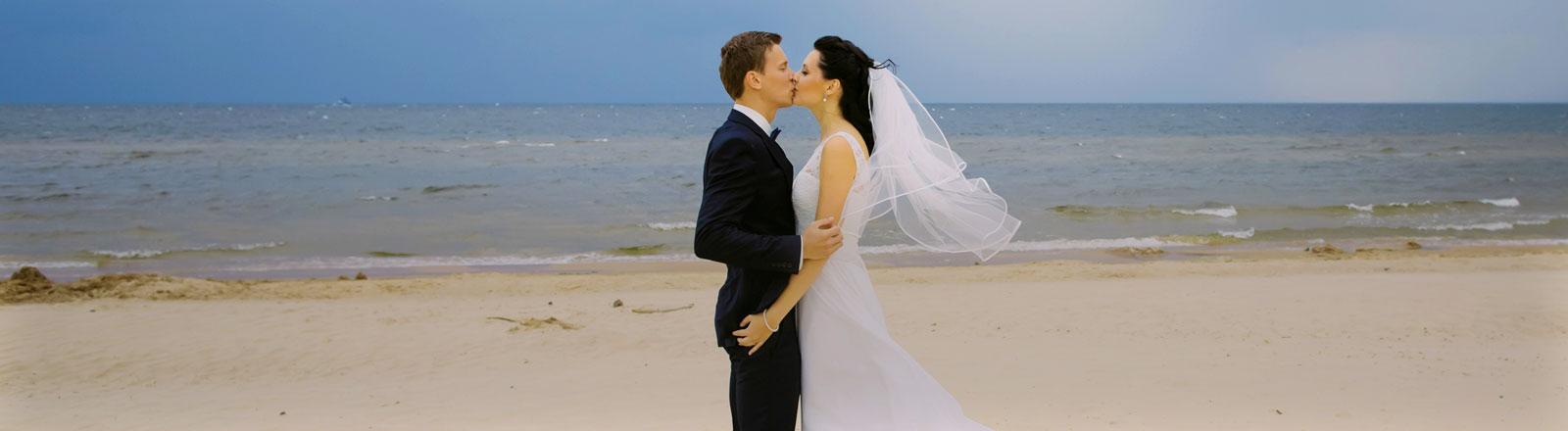 Ein Hochzeitspaar am Strand.