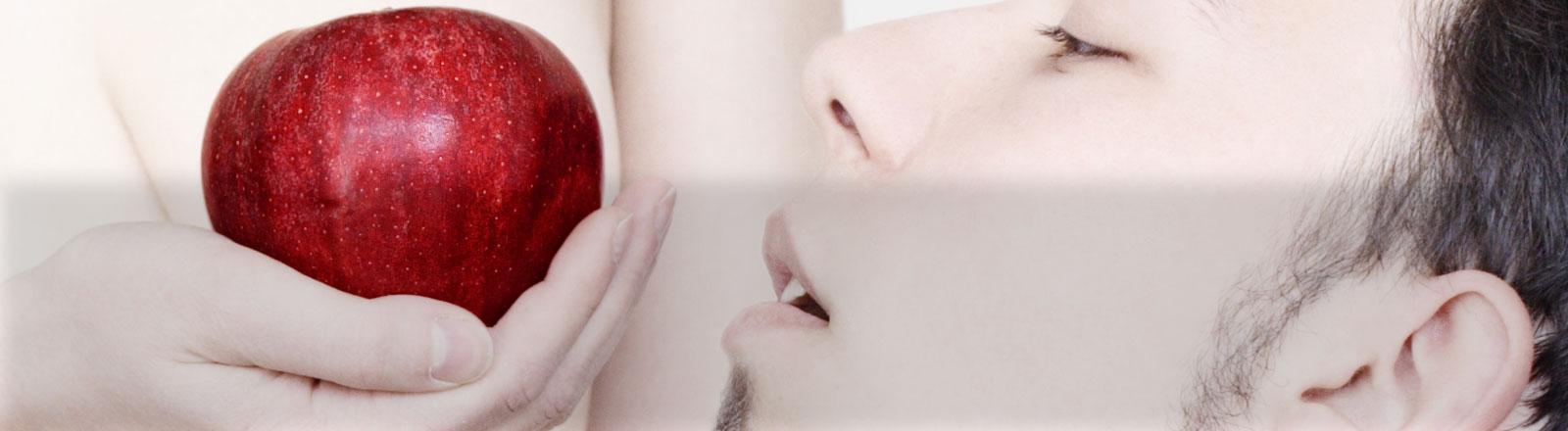 Eine Frau hält einem Mann einen Apfel hin - und zwar vor ihrer Brust.