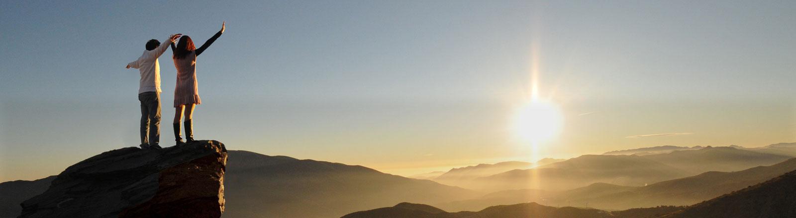 Ein Paar steht auf einem Felsvorsprung und schaut mit nach oben gerissenen Armen in die Sonne.