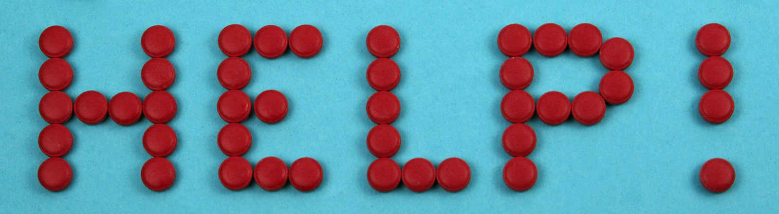 """Symbolbild Tablettensucht: Mit Tabletten ist das Wort """"help"""" geschrieben worden."""