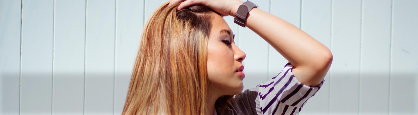 Eine Frau steht im Profil da und streicht sich die Haare aus dem Gesicht.