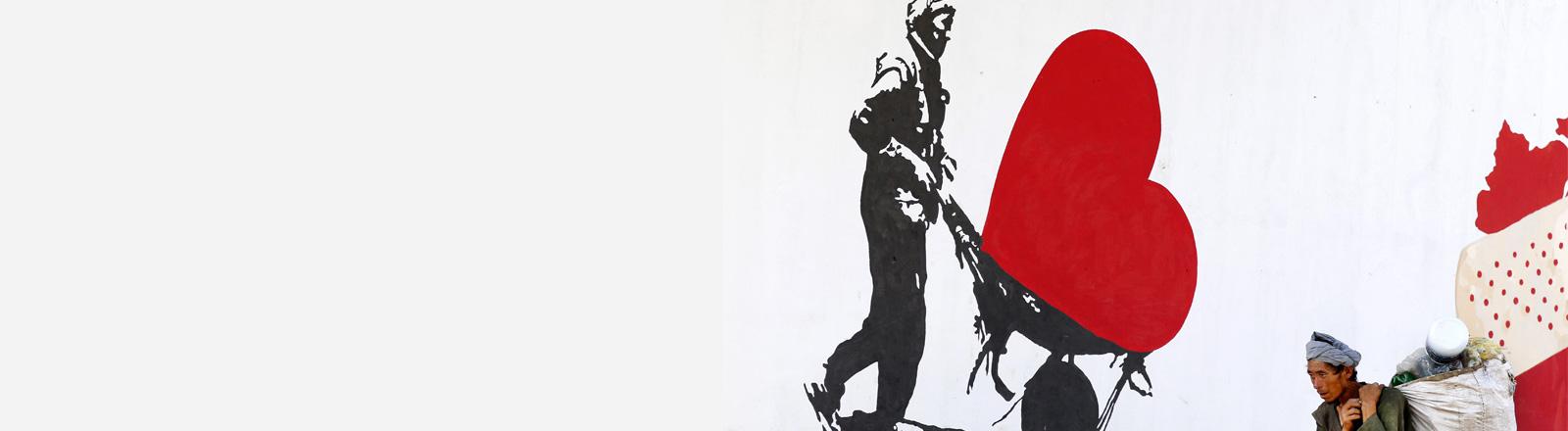 Auf einem Graffiti in Kabul ist ein Mann zu sehen, der ein Herz in einer Schubkarre transportiert.