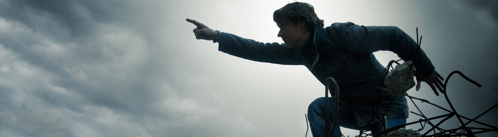 """Ein Mann macht eine """"Vorwärts!""""-Geste und klettert dabei über Ruinen."""