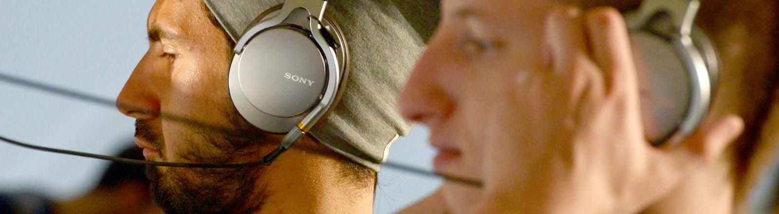 Neue Kopfhörer testen zwei Besucher am 06.09.2014 auf der Elektronikmesse IFA in Berlin auf dem Stand des Unternehmens Sony.