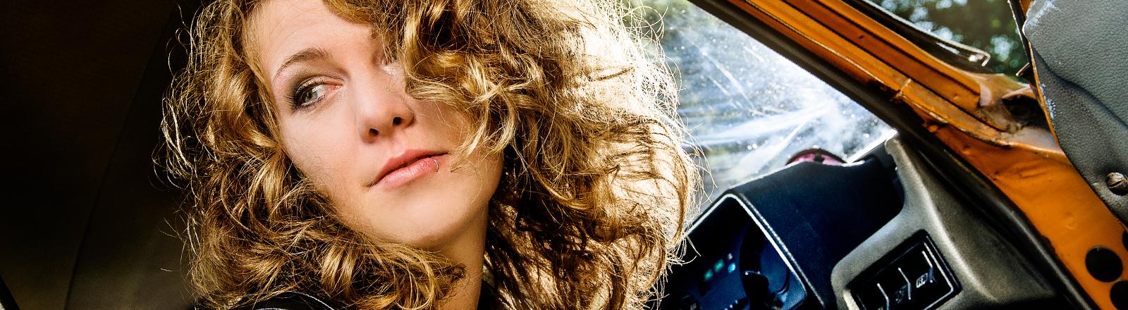 Eine Frau sitzt in einem etwas älteren Auto und guckt halt so rum.