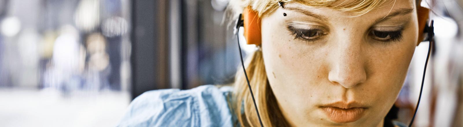 Eine Frau trägt Kopfhörer und konzentriert sich auf den Ton.