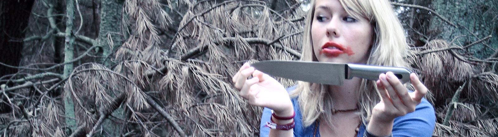 Eine Frau hält ein böse aussehendes Messer in den Händen, ihr Lippenstift ist verschmiert, sie schaut recht verschlagen.