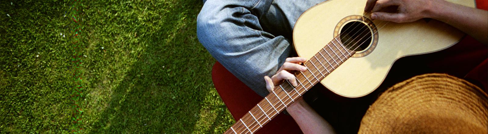 Da spielt jemand ganz entspannt Musik auf seiner Gitarre.