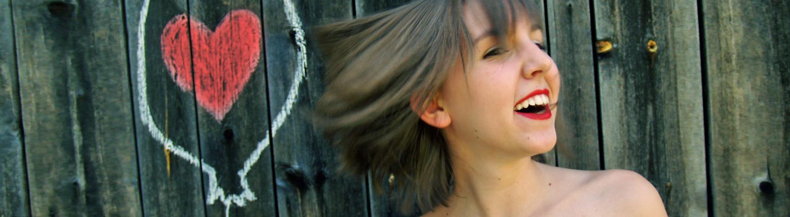 Eine Frau steht glücklich strahlend vor einer Holzwand, neben ihr ist ein Herz aufgemalt.